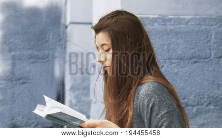 Young beautiful woman enjoying reading interesting books in old center of europe city (Knowledge development education success concept)