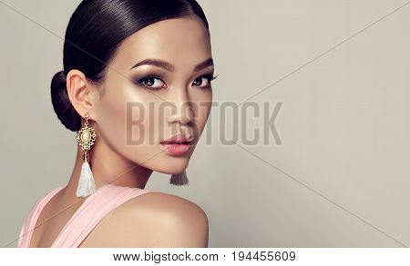 Asian model girl, fashion trend image . Japanese girl with earrings with tassels and a pink dress.Beautiful girl with smoky eyes style  makeup . Fashion woman Portrait . Jewelry and accessories