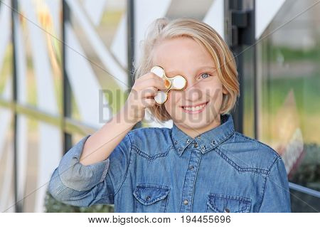 Cheerful cute school aged girl playing with a gold fidget spinner. A popular trendy toy.
