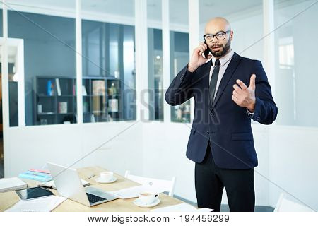 Well-dressed broker consilting client on the phone
