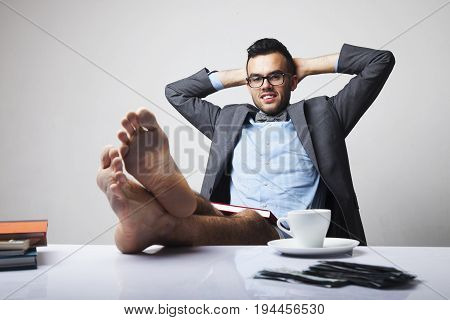 Successful happy young businessman sitting in office with bare feet on desk and relaxing. (Boss business rules officialdom concept)
