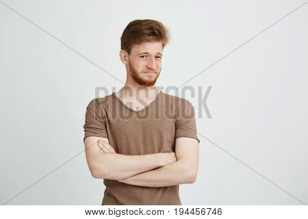 Portrait of young handsome man with beard looking at camera with contempt crossed arms over white background. Copy space.