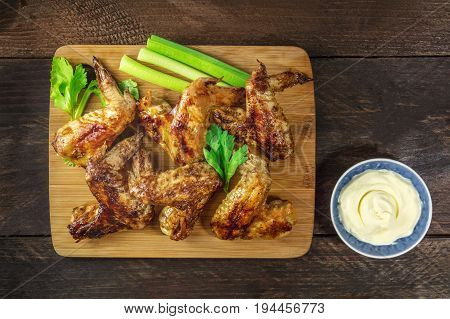 An overhead photo of grilled chicken wings with celery and white sauce, with a place for text