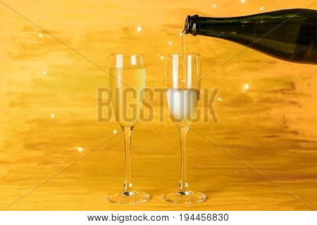 Sparkling wine being poured into glasses on a blurred golden background with shining lights, with a place for text