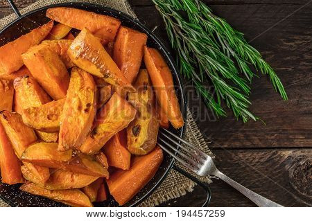 An overhead photo of roasted sweet potatoes in a pan, shot from above on dark rustic wooden textures with rosemary branches, with a place for text and a fork