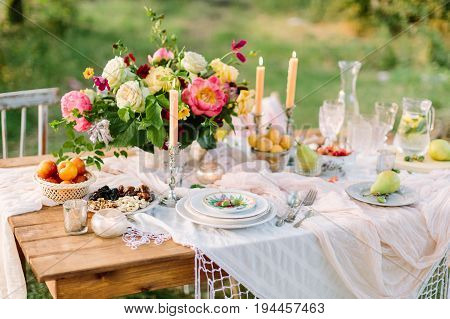 women's day, wedding, celebration, romance, picnic, nature concept - gorgeous table setting with snow white tablecloth, dishes, clear wine-glasses, silver candleholders and various fruits