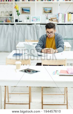 Young learner sitting by desk and texting in smartphone