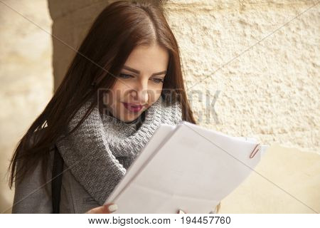 Young beautiful business woman with documents in her hands outdoors. (Business work contract success concept)