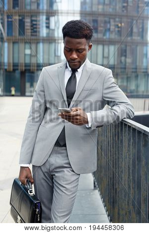 Young salesman texting in urban environment
