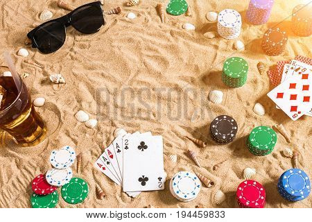 Beachpoker. Chips and cards on the sand. Around the seashells, sunglasses and cold drink in a glass. Top view. Copy space. Flat lay. Sun flare