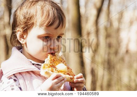 Beautiful little girl enjoying a delicious pizza in nature (food hunger pleasure)