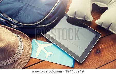 vacation, travel, tourism, technology and objects concept - close up of tablet pc computer and traveler personal stuff