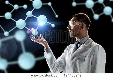 science, biology and people concept - male doctor or scientist in white coat and safety glasses with molecules over black background