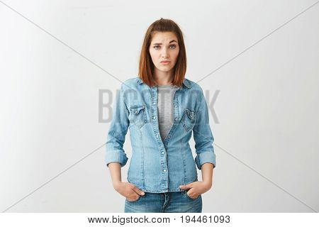 Young pretty brunette girl looking at camera with contempt raising brow up over white background. Copy space.