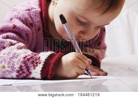 Little beautiful girl writing a letter. close up