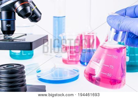 hand of scientist holding flask with colorful liquids. examining samples in laboratory and close up of microscope . laboratory science, clinic and research concept.