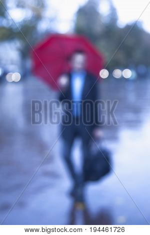 Blurred image. Businessman with red umbrella protecting himself from the rain as symbol of protection from economic crisis (weather business security security concept)