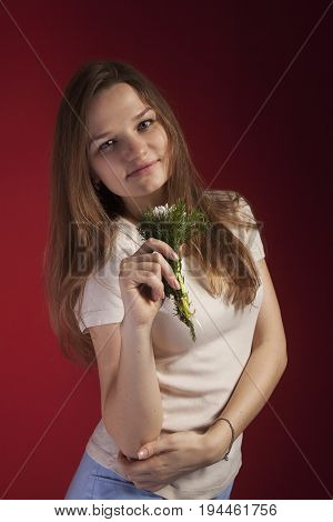 Close-up portrait of Beautiful young woman enjoying and smell a flower on red background.