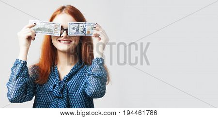 Business Woman covering her mouth with a dollar banknote as symbol of as a symbol of bribery cheating financia and l political manipulation.