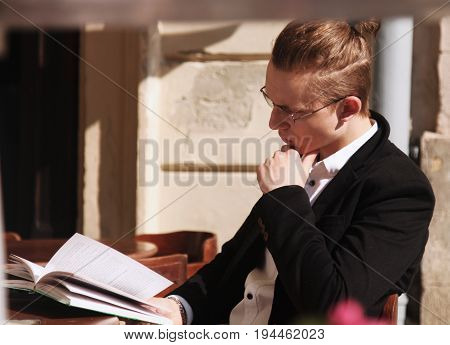 Successful young businessman reading a book in his spare time (freelance time management freedom concept)