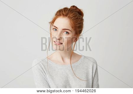 Portrait of beautiful tender redhead girl smiling posing looking at camera over white background. Copy space.