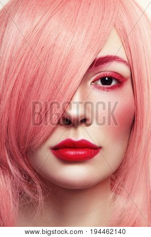 Close-up portrait of young beautiful woman in pink wig
