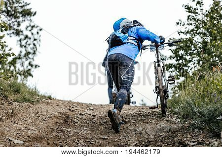 back man cyclist mountain bike in backpack uphill