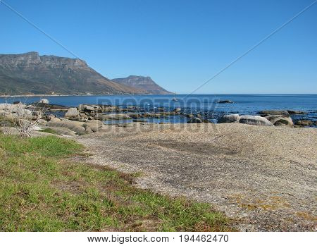 VIEW OF CAMPS BAY, CAPE TOWN, SOUTH AFRICA, WITH HUGE BOULDERS AND LAWN IN THE FORE GROUND AND MOUNTAINS IN THE BACK GROUND 02