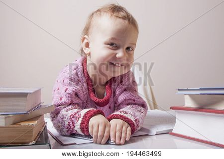 I love my office work. Little beautiful baby girl works with documents. (Humorous Photo)