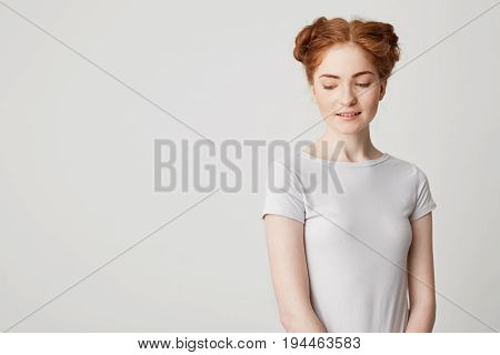 Portrait of shy young pretty redhead girl with buns looking down smiling over white background. Copy space.