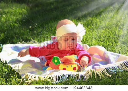 little cute baby girl playing outdoors (developmental toys for children)