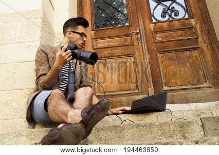 Young photographer looking at photographs on laptop. Photographer selecting photos.