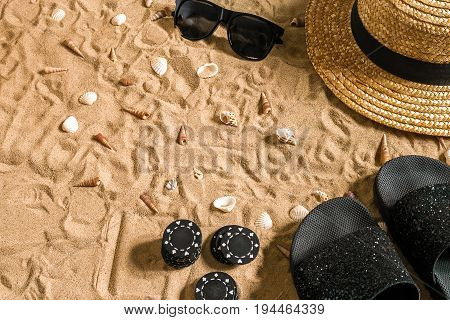 Beachpoker. Chips on the sand. Around the seashells, sunglasses and flip flops. Top view. Copy space. Flat lay