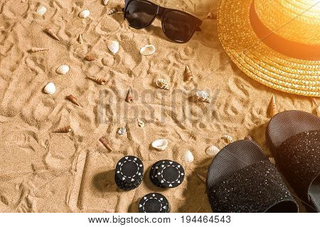 Beachpoker. Chips on the sand. Around the seashells, sunglasses and flip flops. Top view. Copy space. Flat lay. Sun flare