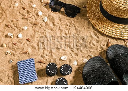 Beachpoker. Chips and cards on the sand. Around the seashells, sunglasses and flip flops. Top view. Copy space. Flat lay
