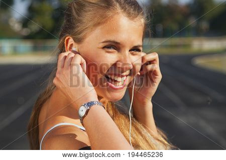 Female fitness model training outside and listening to music using smart phone. Young woman jogging in in running road. Sport lifestyle.