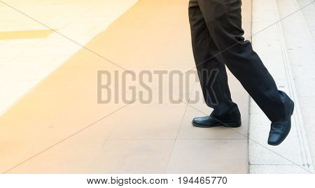 Legs of man wear leather shoes step up from steps and forward to space for move forward and advance concept