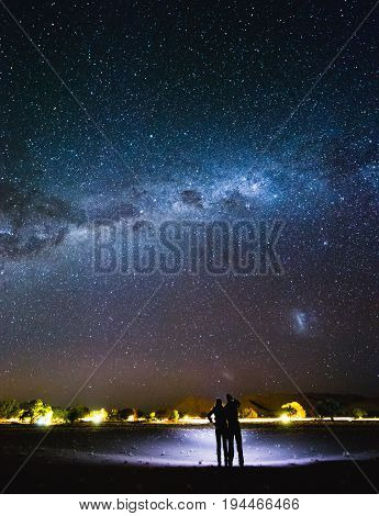 Couple With Flashlight Pointing To The Galaxy At The Sky.  Milky Way Over Sesriem Camping Site, Nami