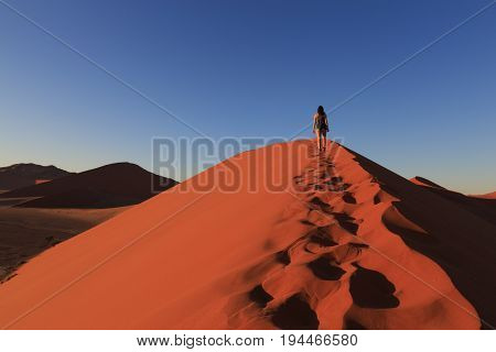 Girl On Sand Dune In Desert During Sunrise.  Sossusvlei, Namib Naukluft National Park, Namibia