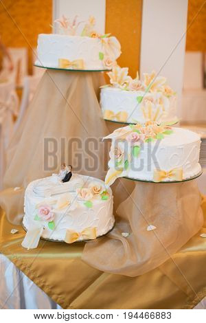 four white wedding cakes on a support decorated with flowers and a figurine of groom and bride in white car. sweets, wedding, party, event concept