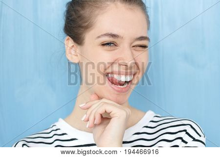 Nice Close-up Portrait Of Young European Girl. Happy Tricky Cute Female With Smiling Face Blinking A