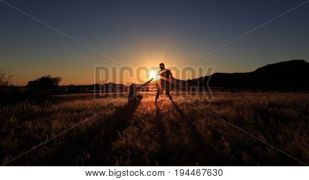 Couple Help Teamwork And Trust Silhouette At African Savanna Landscape. Namibia, South Of Africa.