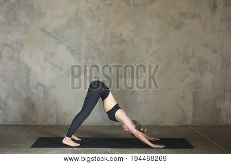 Young Woman Practicing Yoga Downward Facing Dog Pose, Adho Mukha Svanasana Against Texturized Wall /