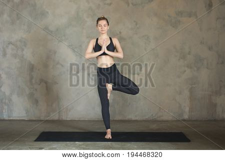 Young Woman Practicing Yoga Tree, Vrikshasana Pose, Hands In Namaste Against Texturized Wall / Urban