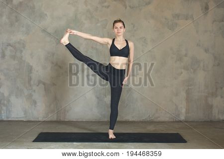 Young Woman Practicing Advanced Extended Right Hand To Big Toe Pose, Utthita Hasta Padangustasana, Y