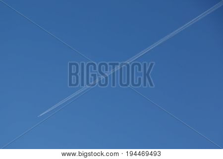 airplane contrail against clear blue sky. Day time.