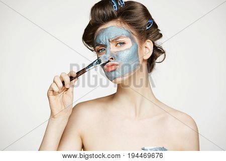Young beautiful girl in hair curlers looking at camera covering face with mack. Facial treatment. Beauty cosmetology and spa. Copy space.