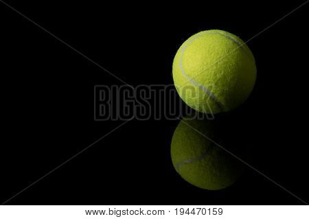 A single tennis ball isolated on a black background