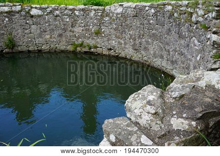 Lichen-covered walls of an ancient stone cistern are reflected in the water on a sunny day in Scotland