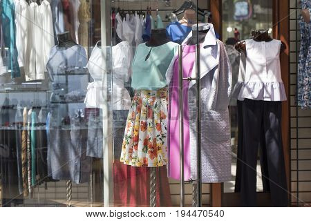 Showcase of a women's clothing store with mannequins.